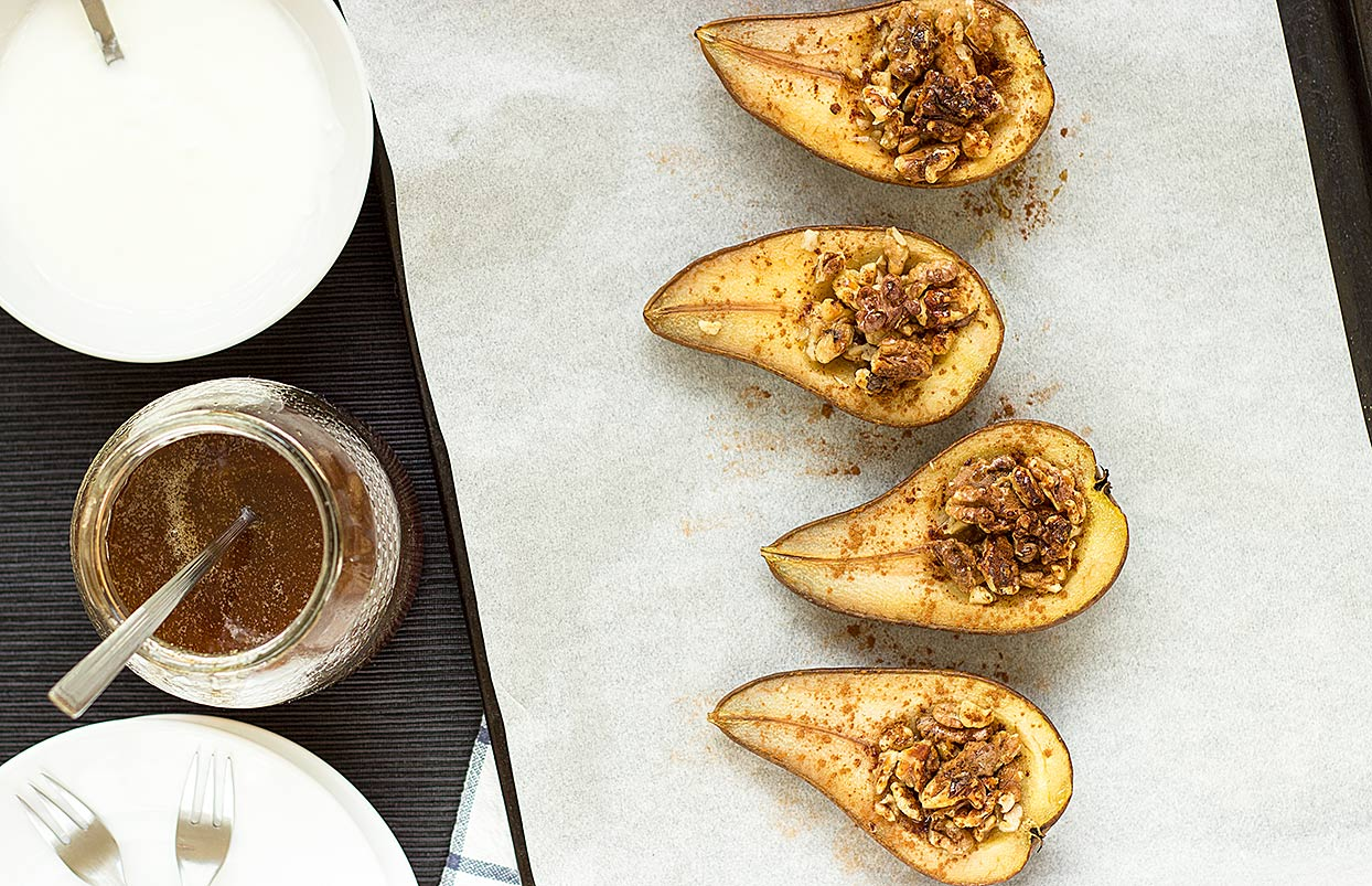 Pears on a baking sheet topped with nuts and cinnamon