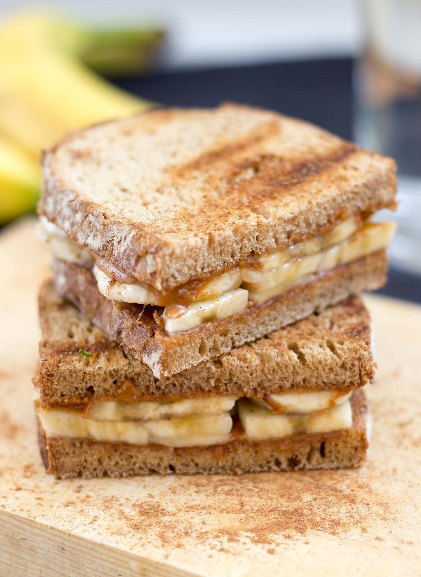 Two peanut butter and banana sandwiches are laid on the chopping board on the blue table with bananas | Hurry The Food Up