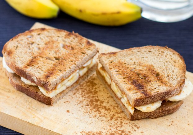 Two sandwiches are served on the chopping board on the blue table with bananas | Hurry The Food Up