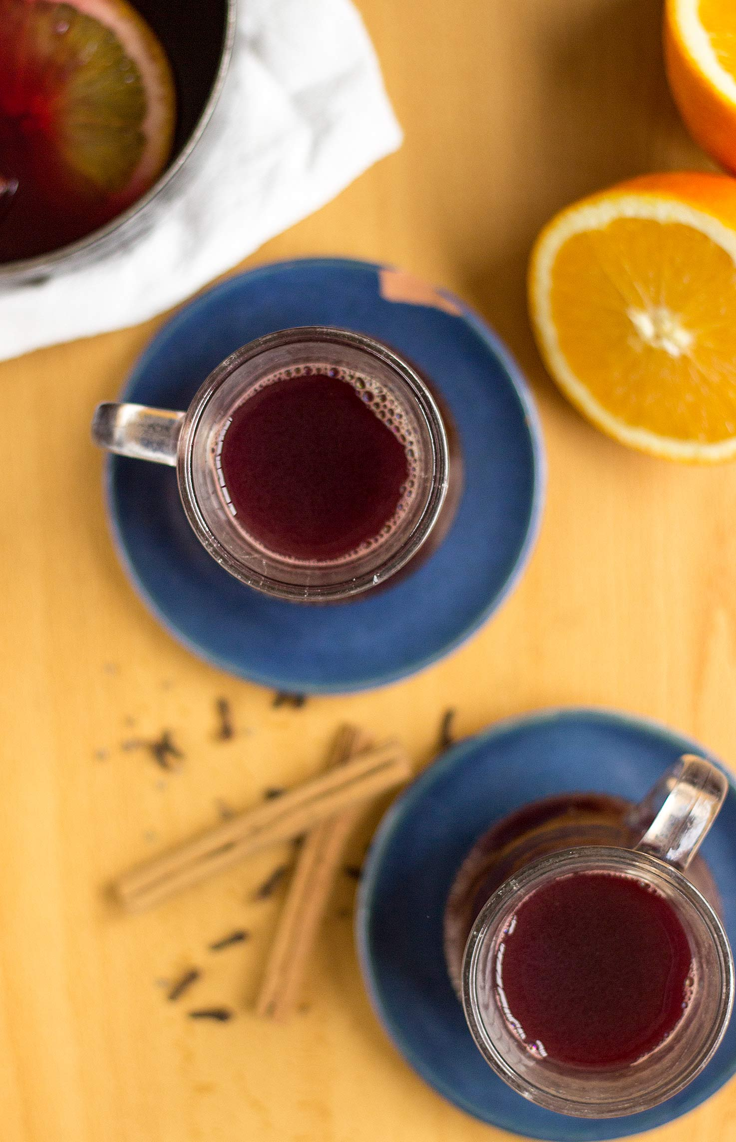 Spiced wine served in 2 glasses on blue plates with orange and cinnamon sticks on the table | Hurry The Food Up