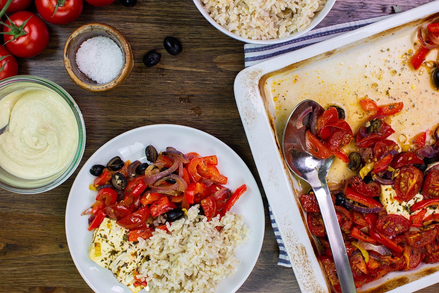 The feta veggie bake is served with rice on the plate on a table with hummus, salt, tomatoes, olives, baking tray on a tea towel and a deep plate with rice #olive oil #basil, dried | hurrythefoodup.com