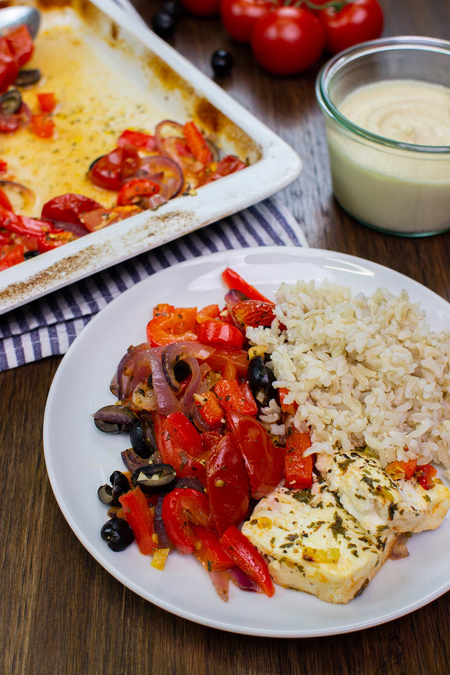 The dish is served with rice on the plate on a table with hummus, tomatoes, olives and baking tray on a towel #brown rice #feta cheese   hurrythefoodup.com