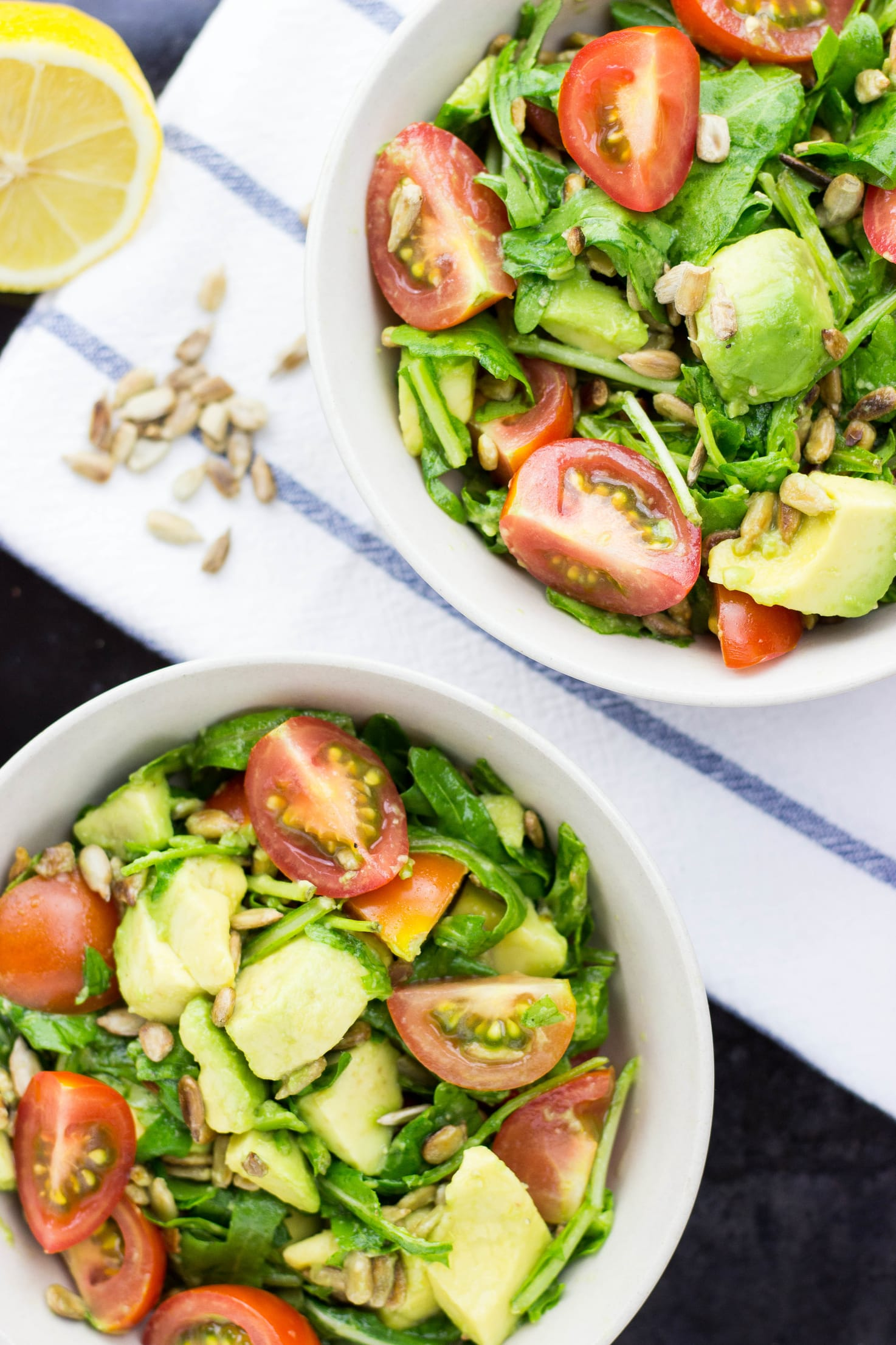 Two bowls of avocado and tomato salad on a blue and white table cloth, with sunflower seeds and lemon scattered around | Hurry The Food Up