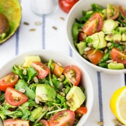 Two bowls of salad are on a blue and white striped table cloth, with an empty avocado shell, salt and pepper grinders and half a lemon   Hurry The Food Up