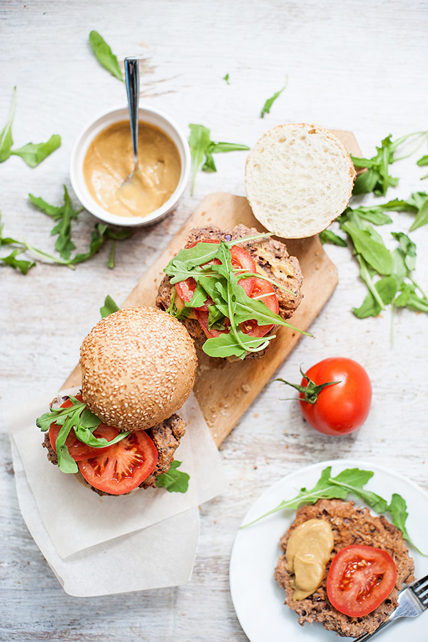 Homemade veggie burgers in buns are served in a chopping board with lettuce, tomatoes and sauce | Hurry The Food Up