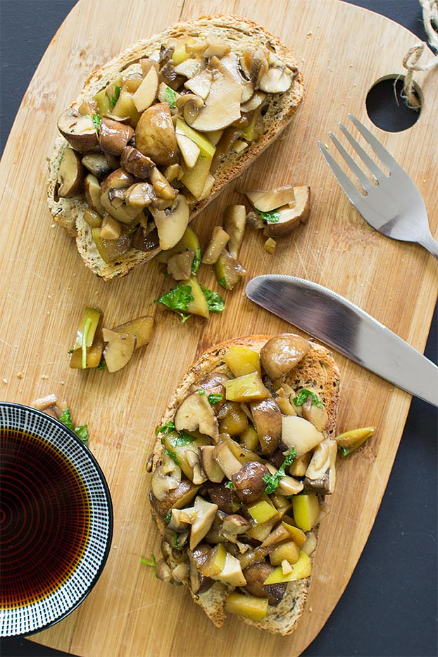 The toasts are on the chopping board on a table with soy sauce and fork with knife #garlic #parsley | hurrythefoodup.com