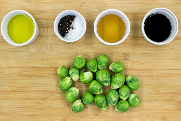 Brussel sprouts and ingredients for balsamic glaze on a chopping board