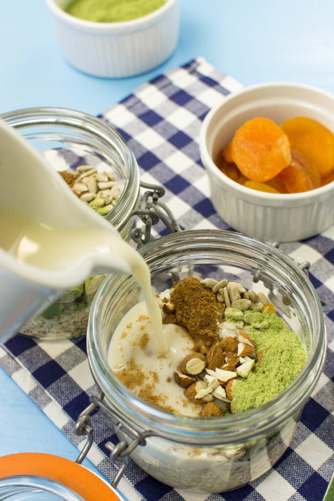 The almond milk is pouring in to the jar with the ingredients of the Vegan IRONMAN Oatmeal. There is also another jar with the ingredients and a bowl with dried apricots | Hurry The Food Up