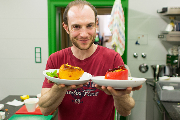 Vegan Stuffed Peppers – Packed with Protein - Dave is holding the plates with the stuffed peppers #salt yeast #basil leaves | hurrythefoodup.com