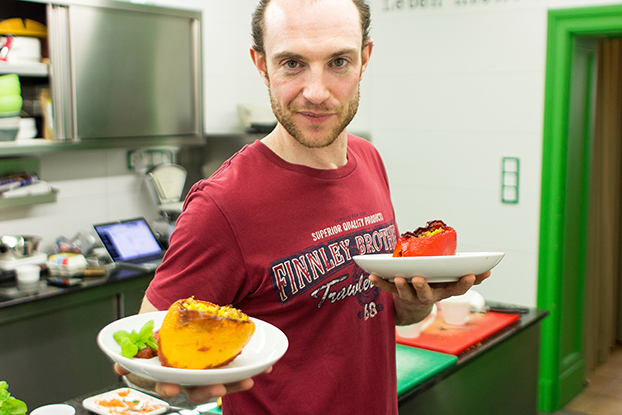 Vegan Stuffed Peppers – Packed with Protein - Dave is holding two plates with the stuffed peppers #bell peppers #sugar | hurrythefoodup.com