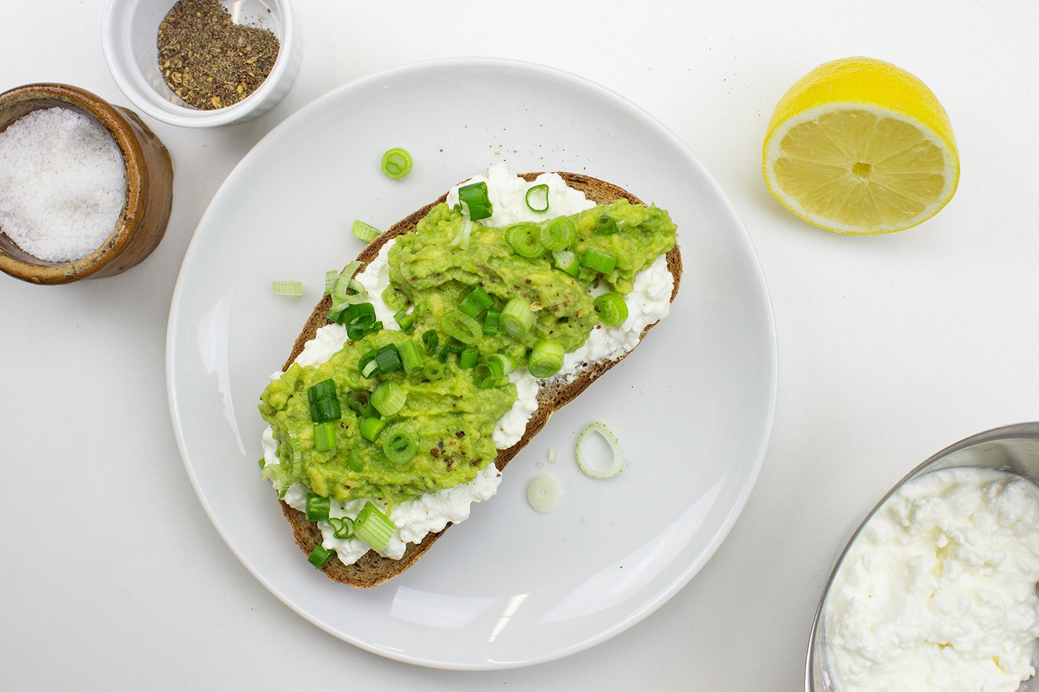 The toast is on the plate on a table with salt, pepper, lemon and cottage cheese in the bowl #bread #avocado | hurrythefoodup.com