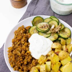 The Buddha bowl is served with cucumber salad on the table on a plates with towel, salt and sauce #vegetable broth #brown lentils | hurrythefoodup.com