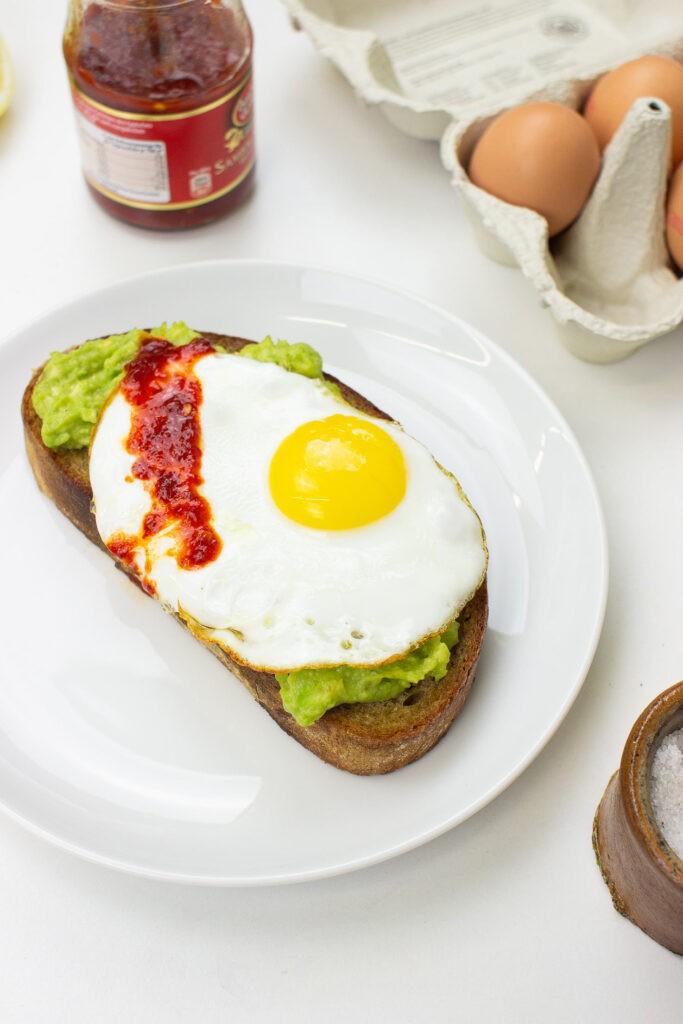 The avocado toast is on the plate on a table with salt, eggs and Sriracha in the jar #bread #avocado | hurrythefoodup.com