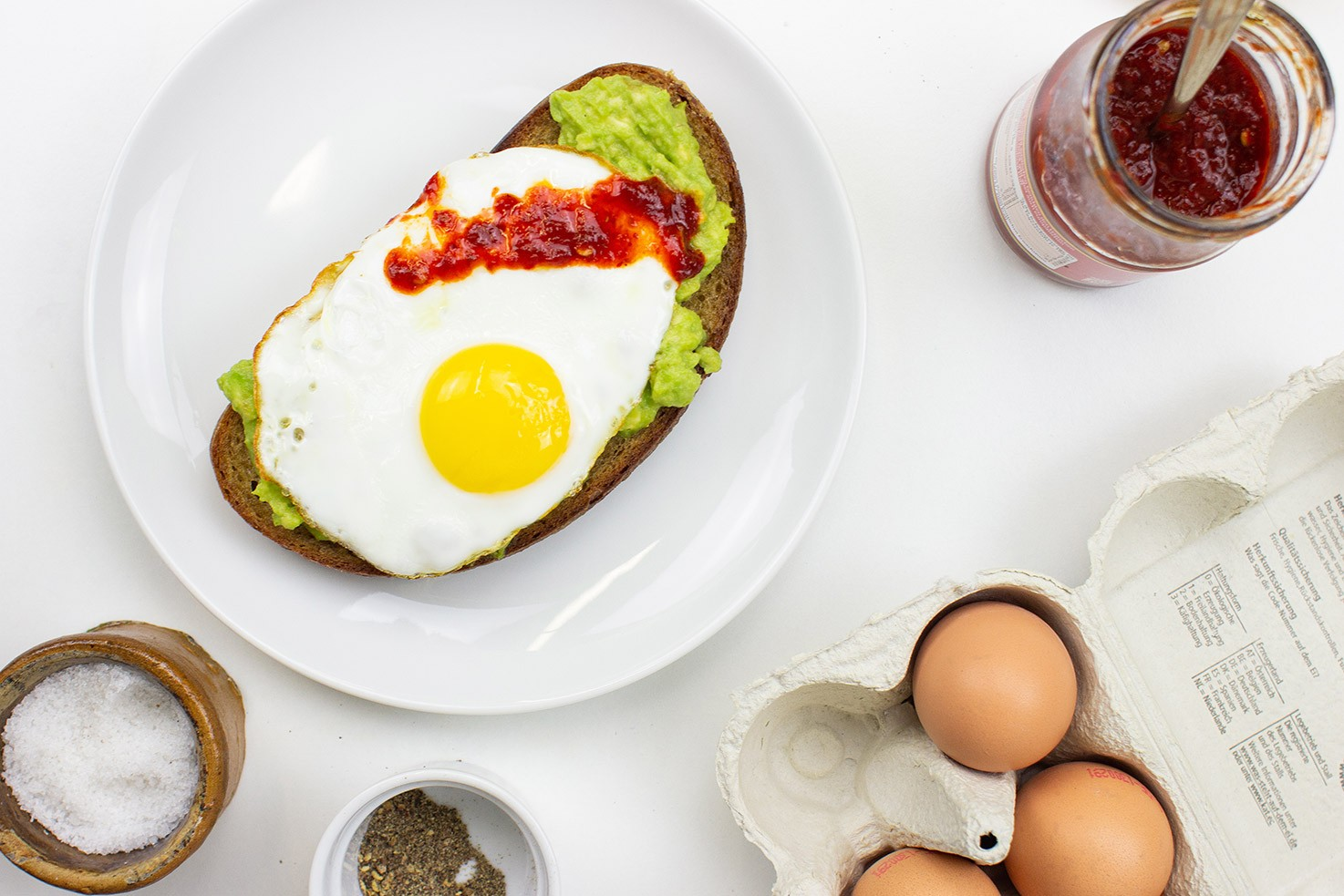 The avocado toast is on the plate on a table with salt, pepper, eggs and Sriracha in the jar #lemon #olive oil | hurrythefoodup.com