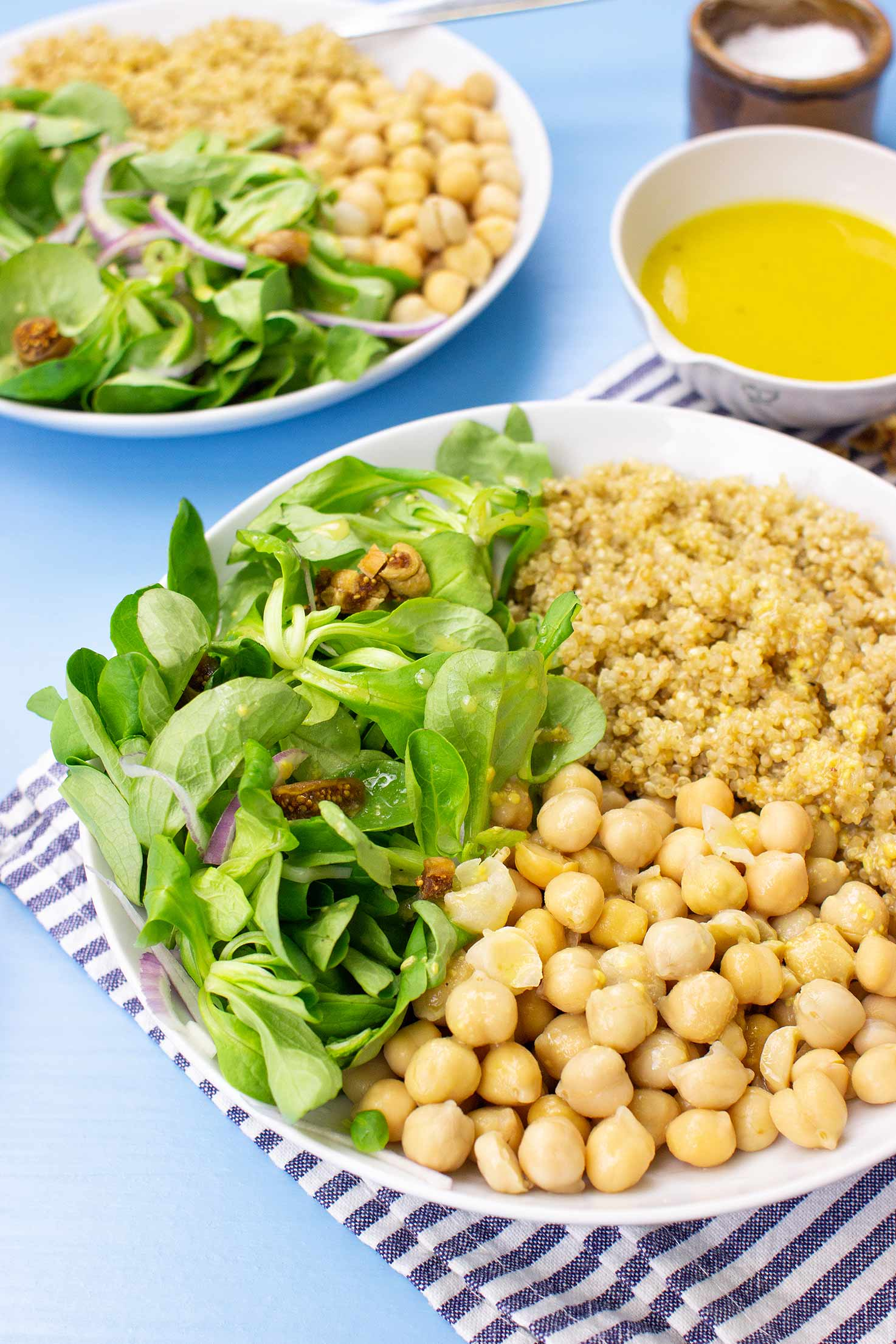 The meal with corn salad are on the table on 2 plates with towel, salt and dressing #olive oil #white vinegar   hurrythefoodup.com