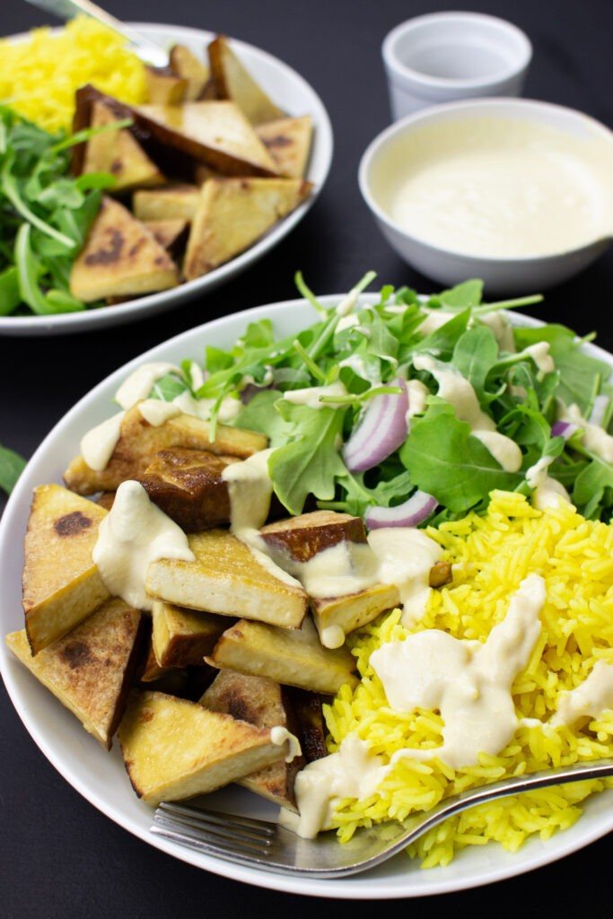 Smoked Tofu & Hummus Buddha Bowl with lamb's lettuce are on the black table on 2 plates with forks, pepper and hummus #smoked tofu #olive oil | hurrythefoodup.com