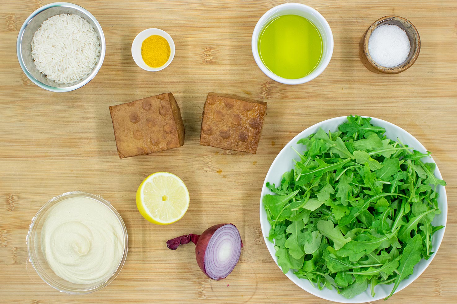 The meal ingredients are on the chopping board - rice, tofu, lamb's lettuce, turmeric, hummus, onion #lemon juice #salt | hurrythefoodup.com