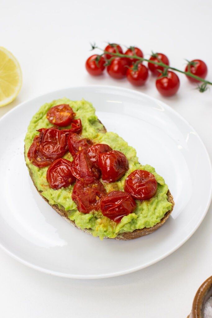 Tomato Avocado Toast is on the plate on a table with salt, lemon and cherry tomatoes #bread #olive oil | hurrythefoodup.com