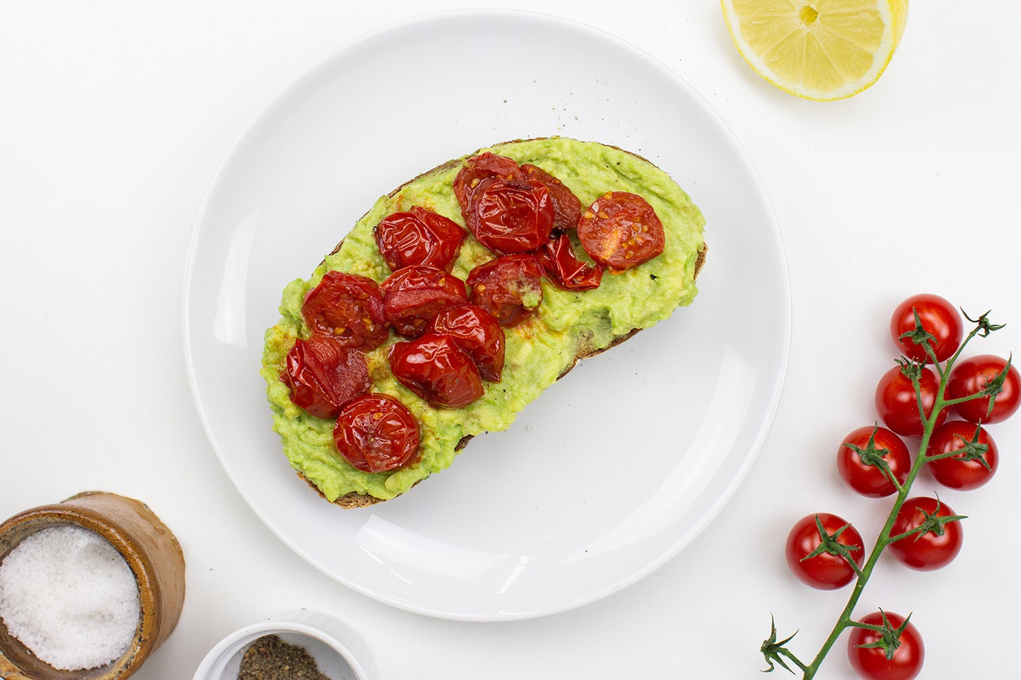 The toast is on the plate on a table with salt, pepper, lemon and cherry tomatoes #avocado #lemon juice | hurrythefoodup.com