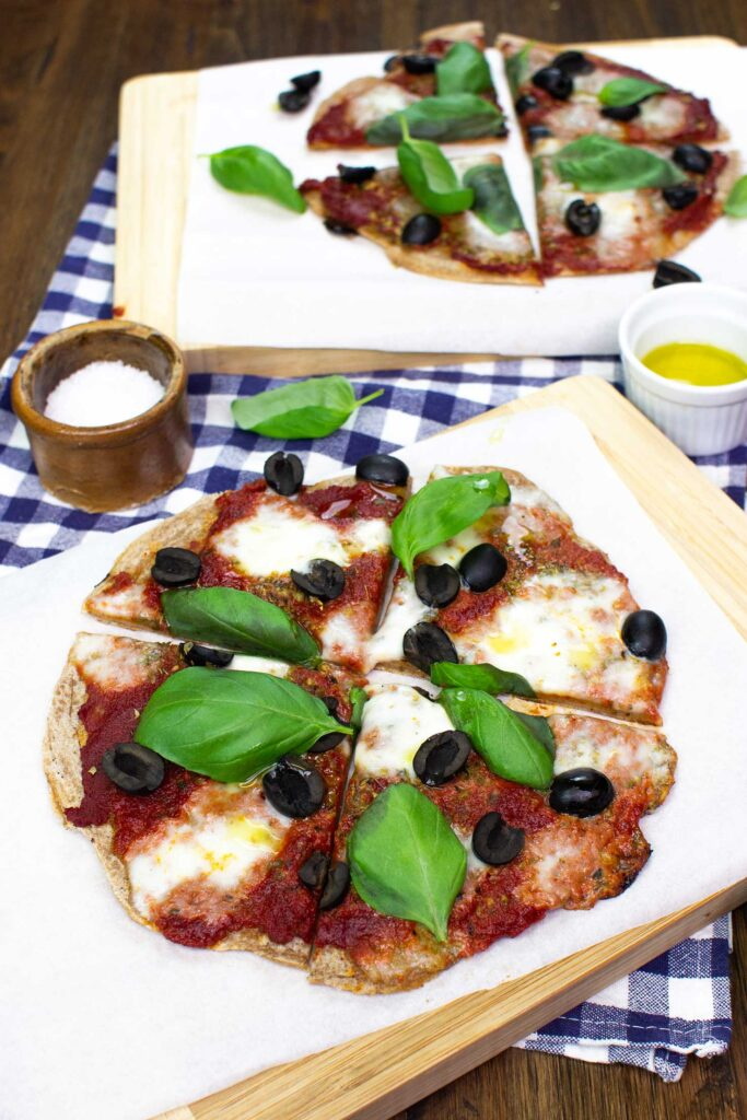 Two Pancake Pizzas are on the black table on two wooden boards with towel, salt and olive oil #flour #water | hurrythefoodup.com