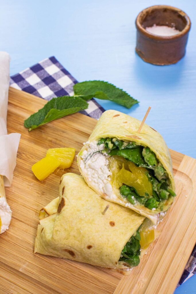 The two pieces of Pineapple Cottage Breakfast Burritos, two pieces of pineapple and two mint leaves are on the chopping board on a towel on the blue table with salt #tortilla wraps #spinach | hurrythefoodup.com