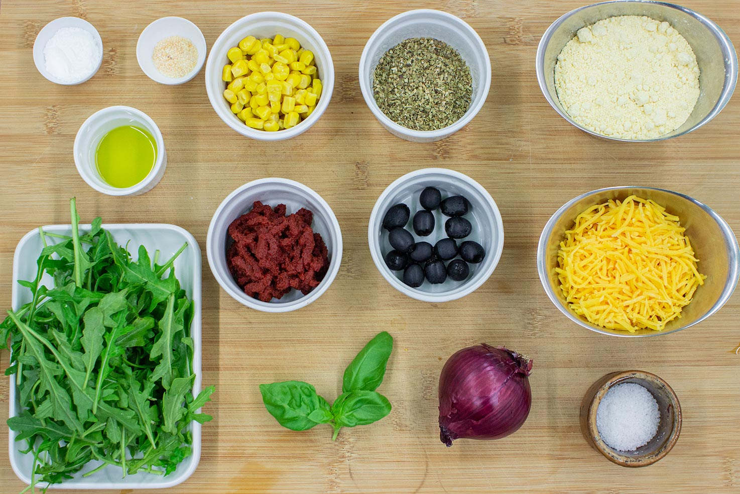The Socca Pizza ingredients are on the chopping board - chickpea flour, garlic powder, baking powder, tomato paste, dried oregano, red onion, cheddar cheese, sweetcorn, olives, arugula, basil #sweetcorn #olive oil | hurrythefoodup.com