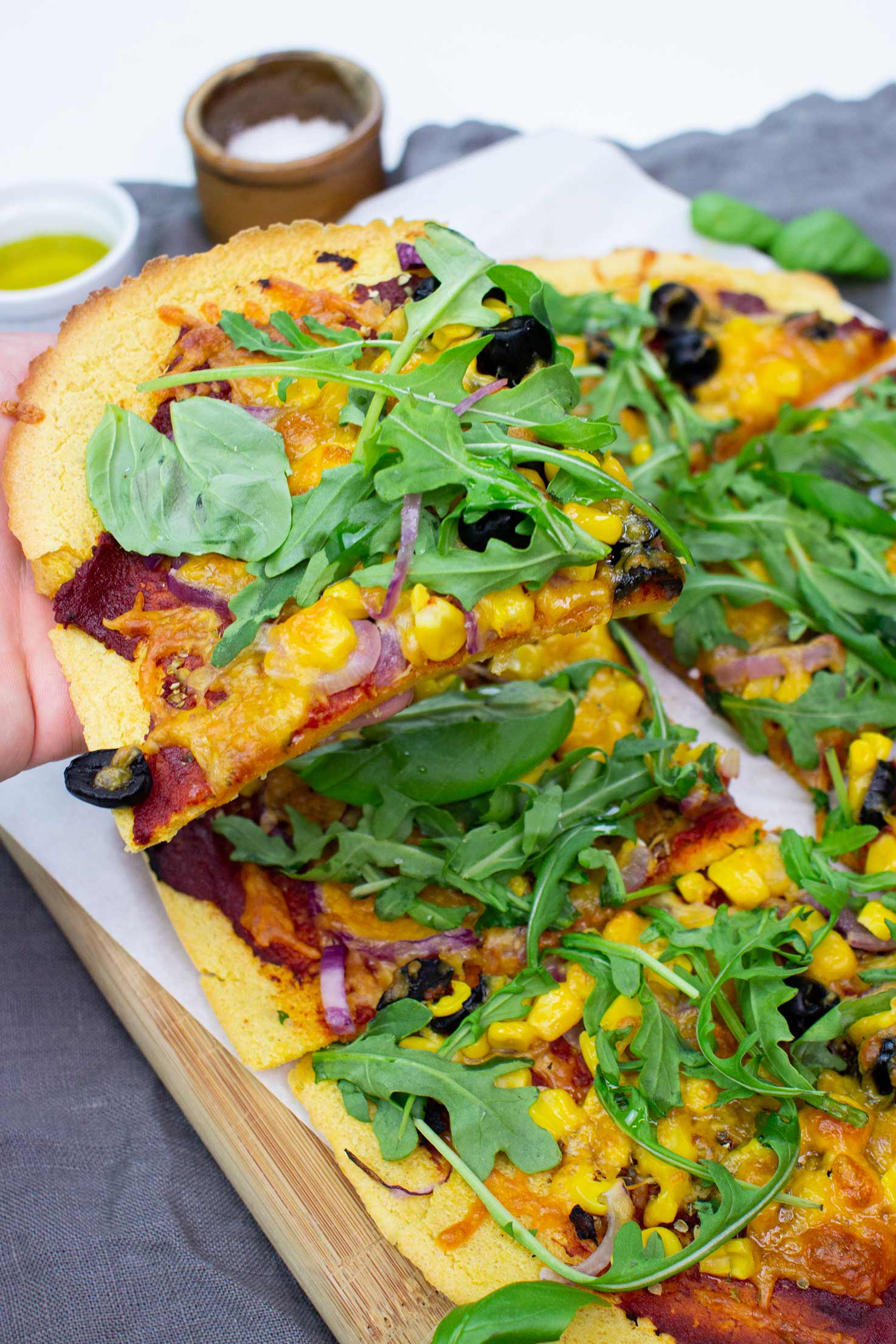 The pizza is on the paper on a chopping board on a towel with olive oil and salt, and Dave is holding a piece of pizza #baking powder #oil | hurrythefoodup.com