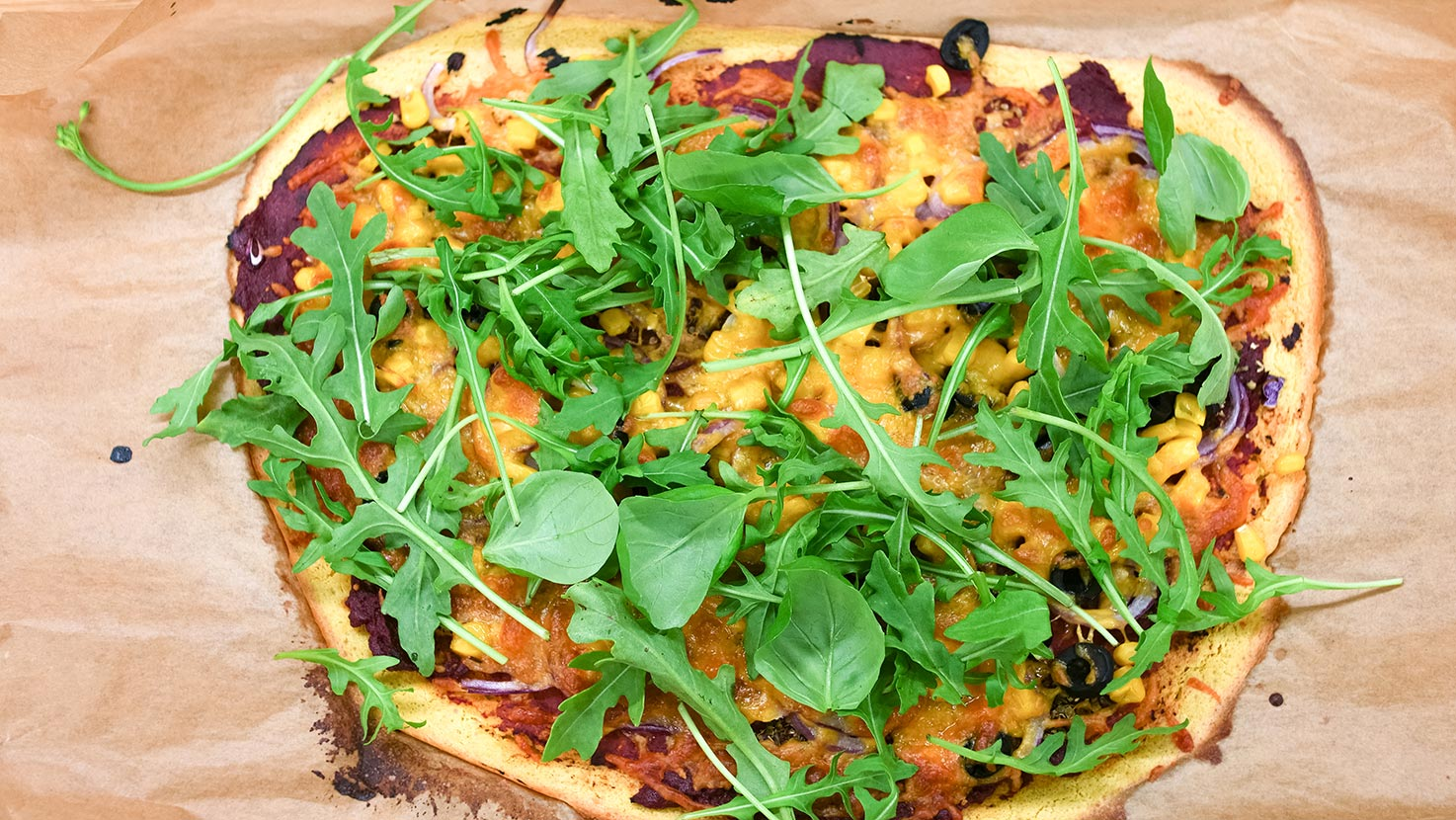 The garnished pizza with arugula/rocket is ready on the parchment paper in a baking tray #oregano #garlic powder | hurrythefoodup.com