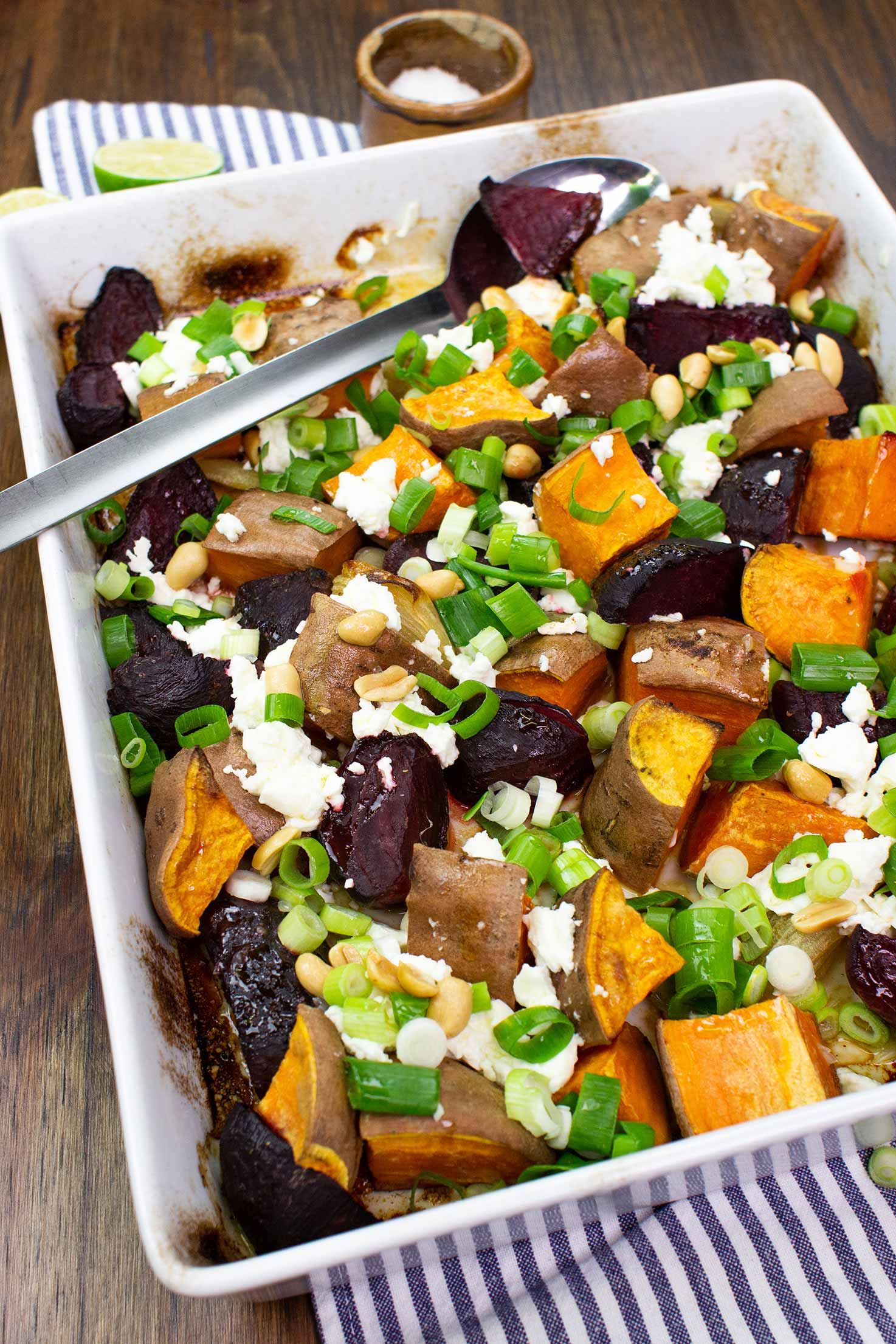 The meal is ready in the baking tray with spoon on a towel with salt and two pieces of lime on the table #sweet potatoes #beets | hurrythefoodup.com