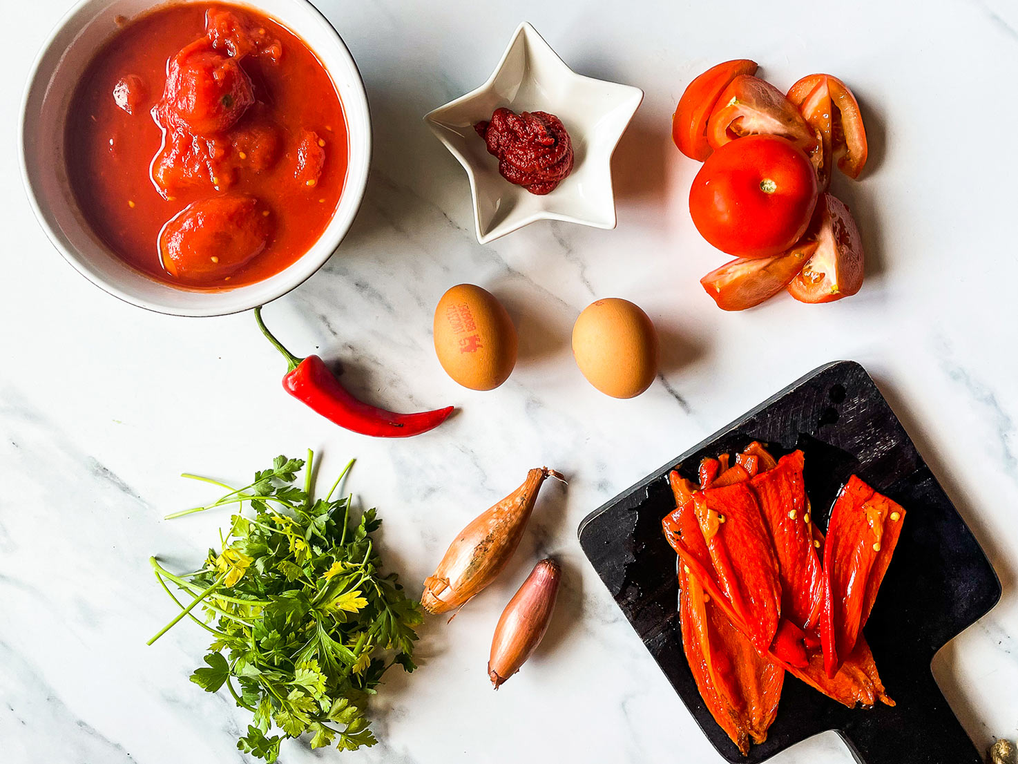 The ingredients are on the table - red onion, tomatoes, tomato passata, eggs and red chili #pepper #bread | hurrythefoodup.com