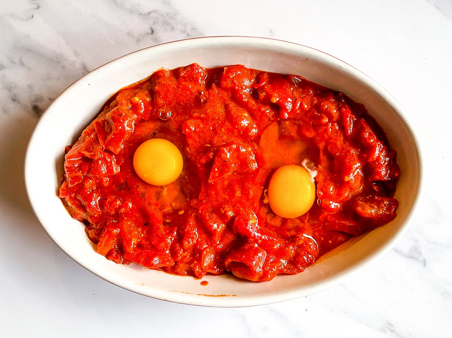 The tomato mixture is transferred into the ovenproof dish with eggs that is on the table #tomato passata #olive oil | hurrythefoodup.com
