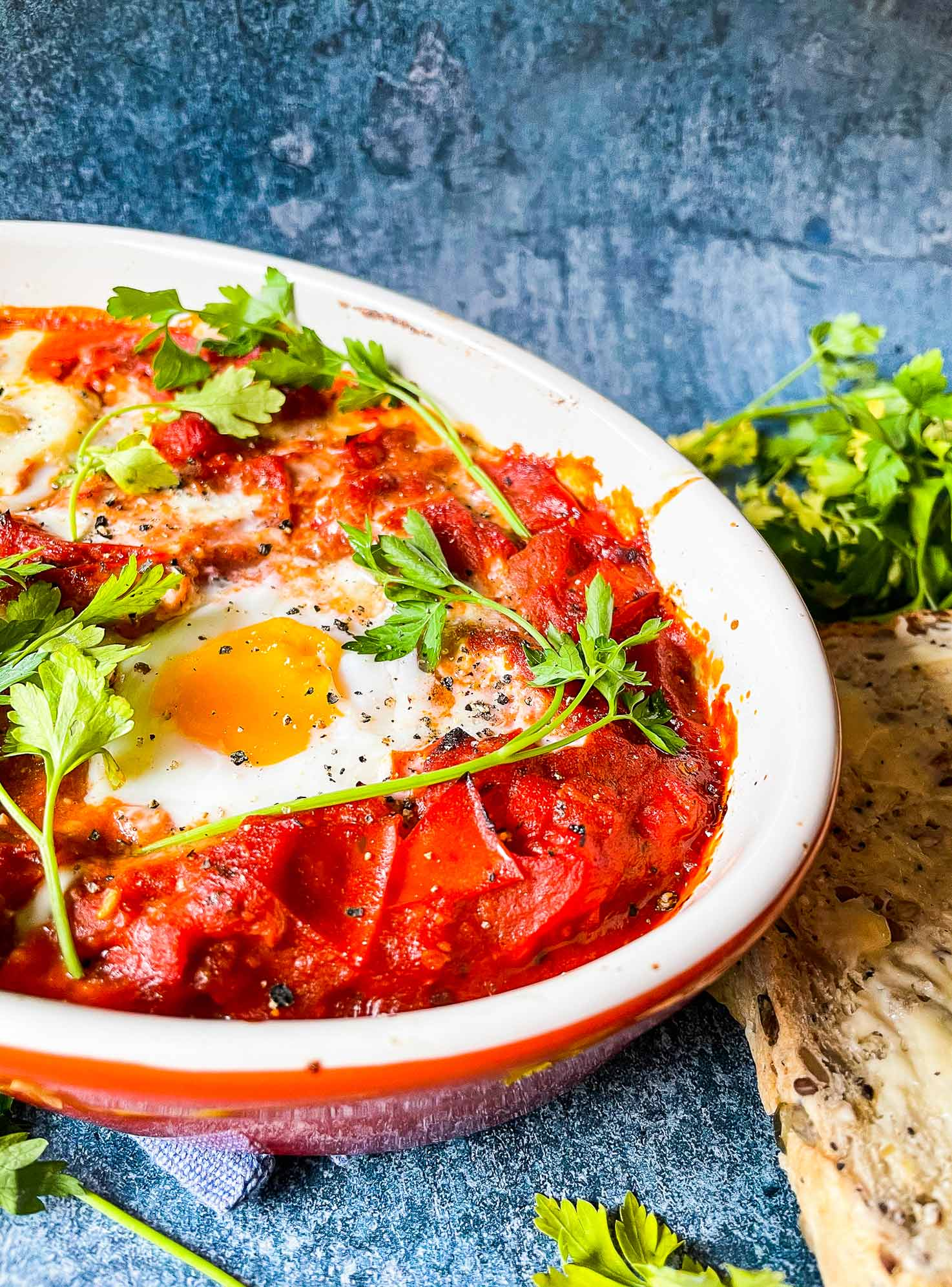 Vegetarian Shakshuka is served on the blue table with parsley and bread #eggs #red onion | hurrythefoodup.com