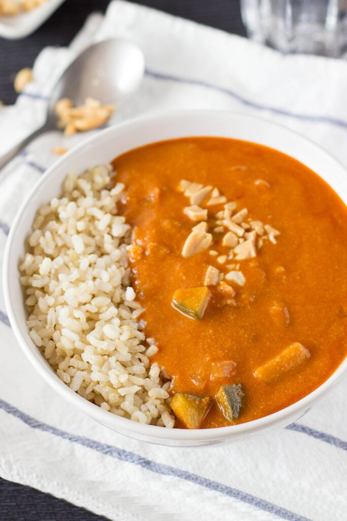 African Peanut Soup is served in the bowl on the white towel with tablespoon | Hurry The Food Up