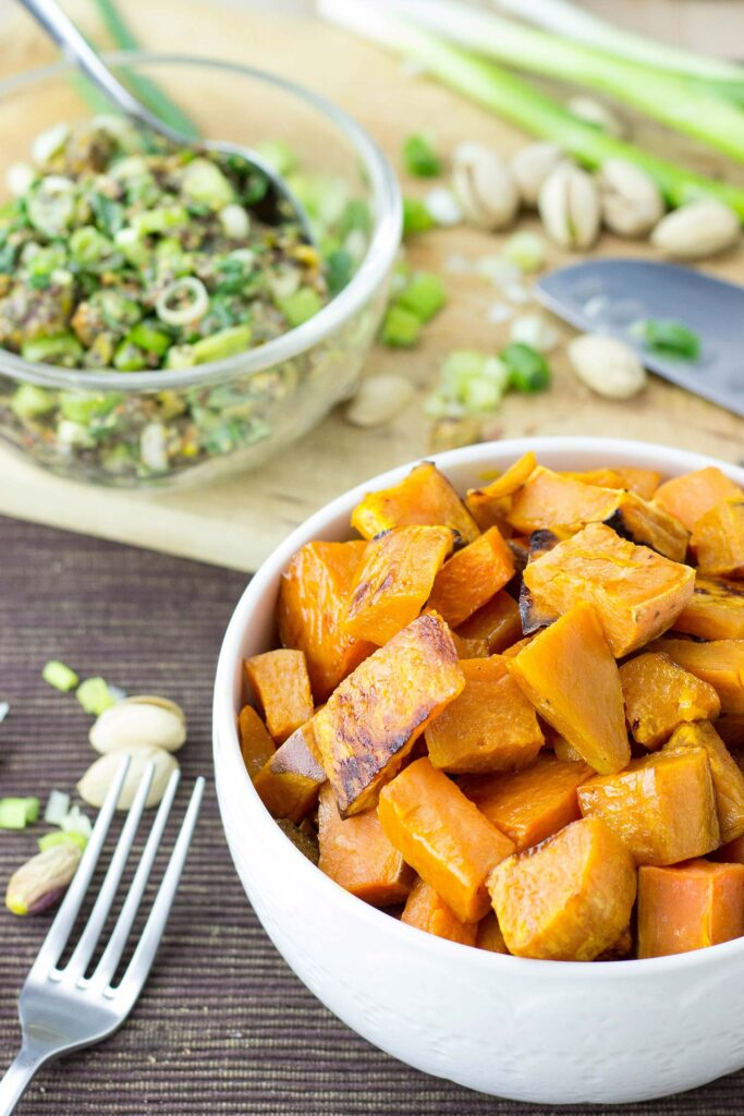 Roasted sweet potato cubes are in the bowl on the table with a piquant pistachio dressing on the chopping board | Hurry The Food Up