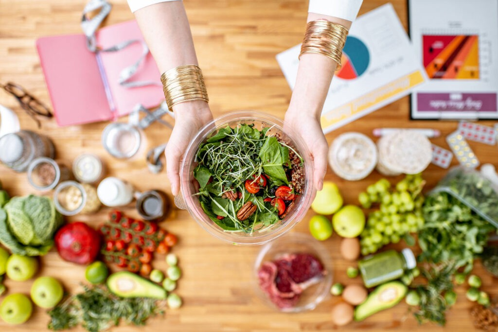 The nutritionist is showing the dish in the bowl under the table with fruits and vegetables | Hurry The Food Up