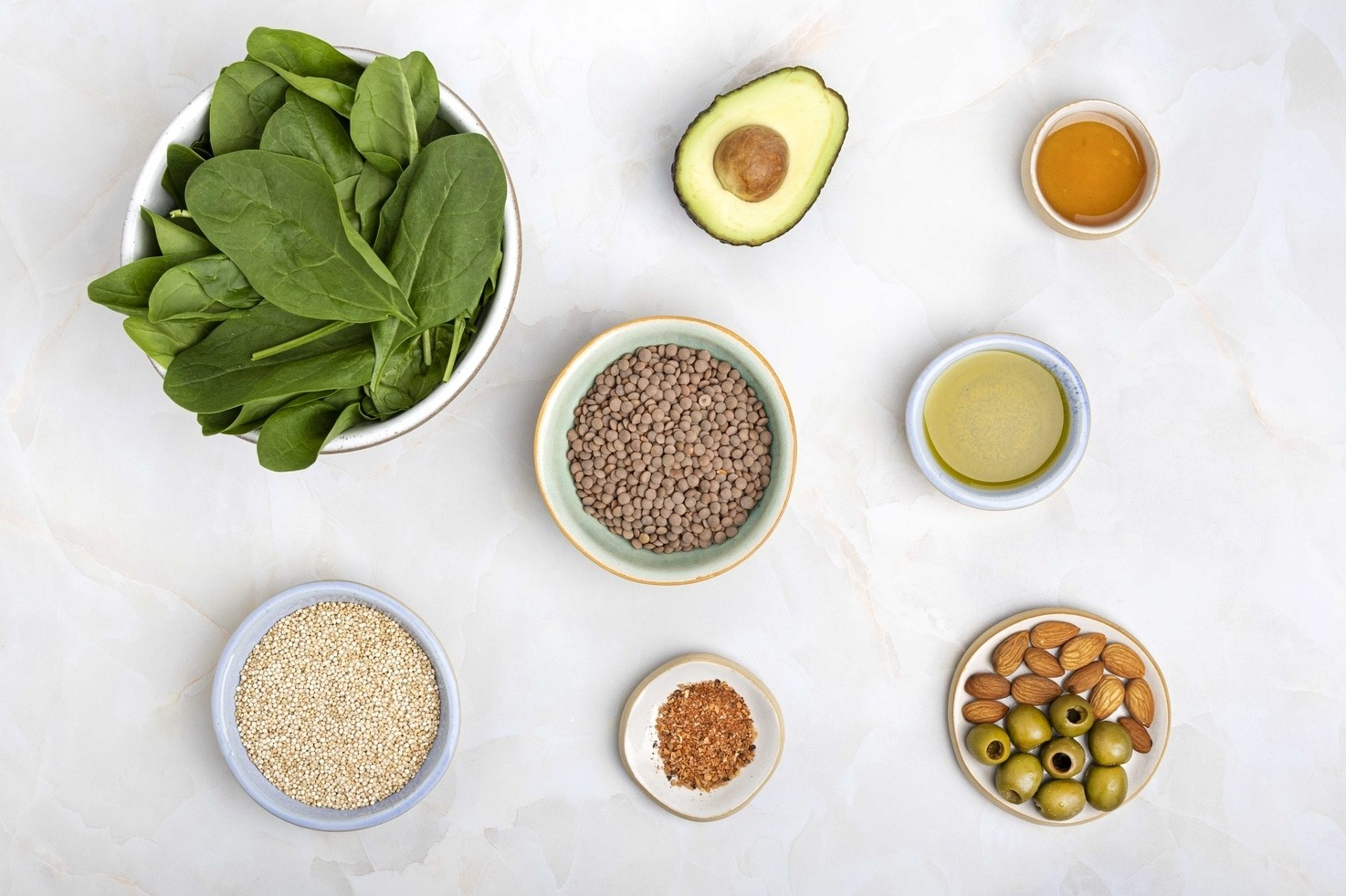 The salad ingredients such as quinoa, red lentils, avocado, olive oil, almonds, olives, spinach etc.   Hurry The Food Up