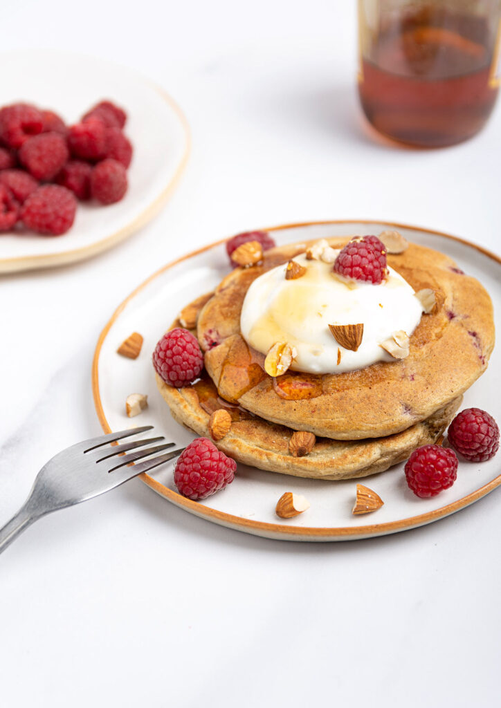 Raspberry low calorie pancakes are served on the white plate with fork and topped with yogurt, almonds and raspberries | Hurry The Food Up