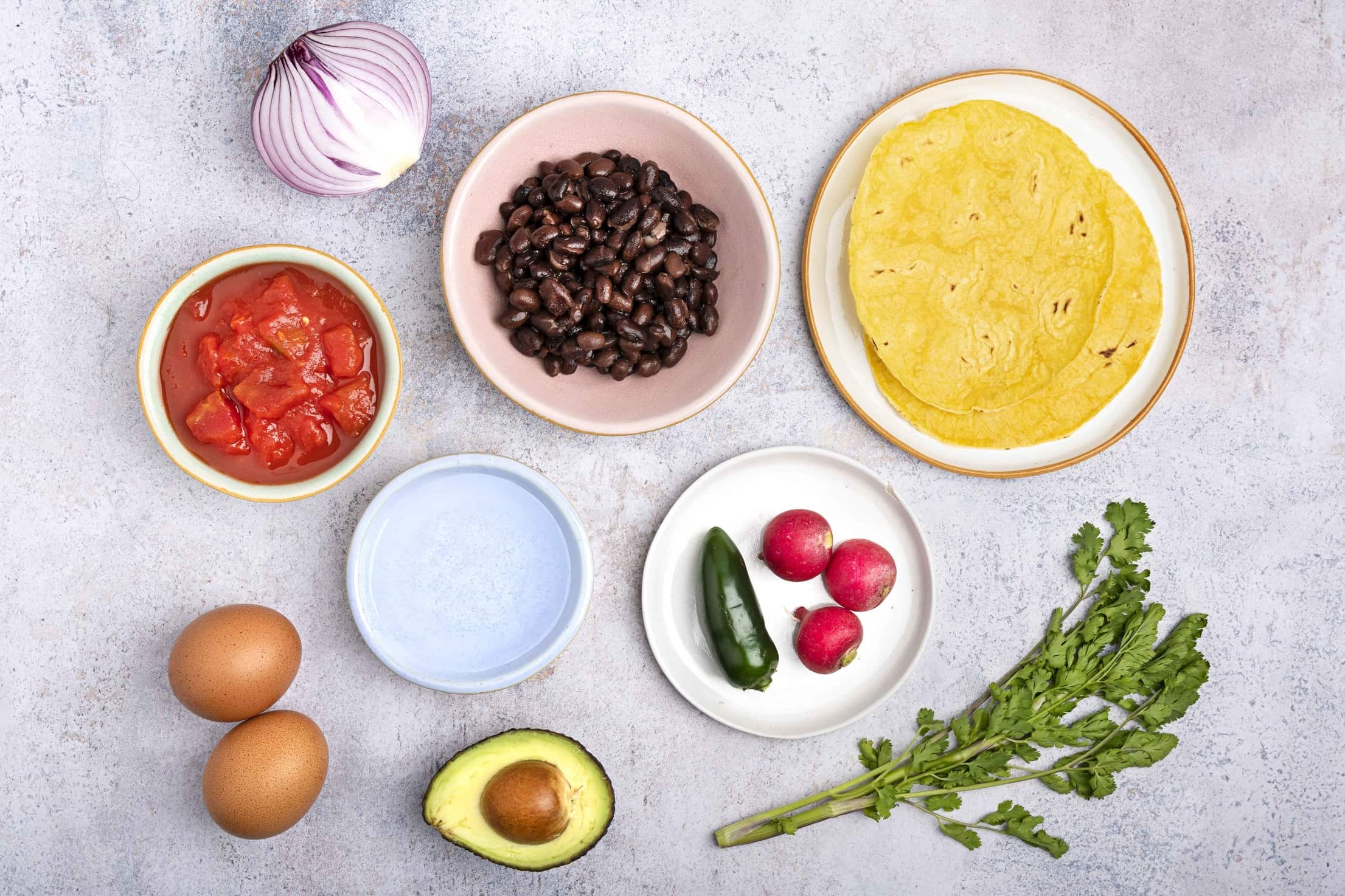 The ingredients for huevos rancheros laid out on a table, including tortillas, black beans, red onion, chopped tomatoes, radishes, jalapeños, eggs, avocado and coriander   Hurry The Food Up