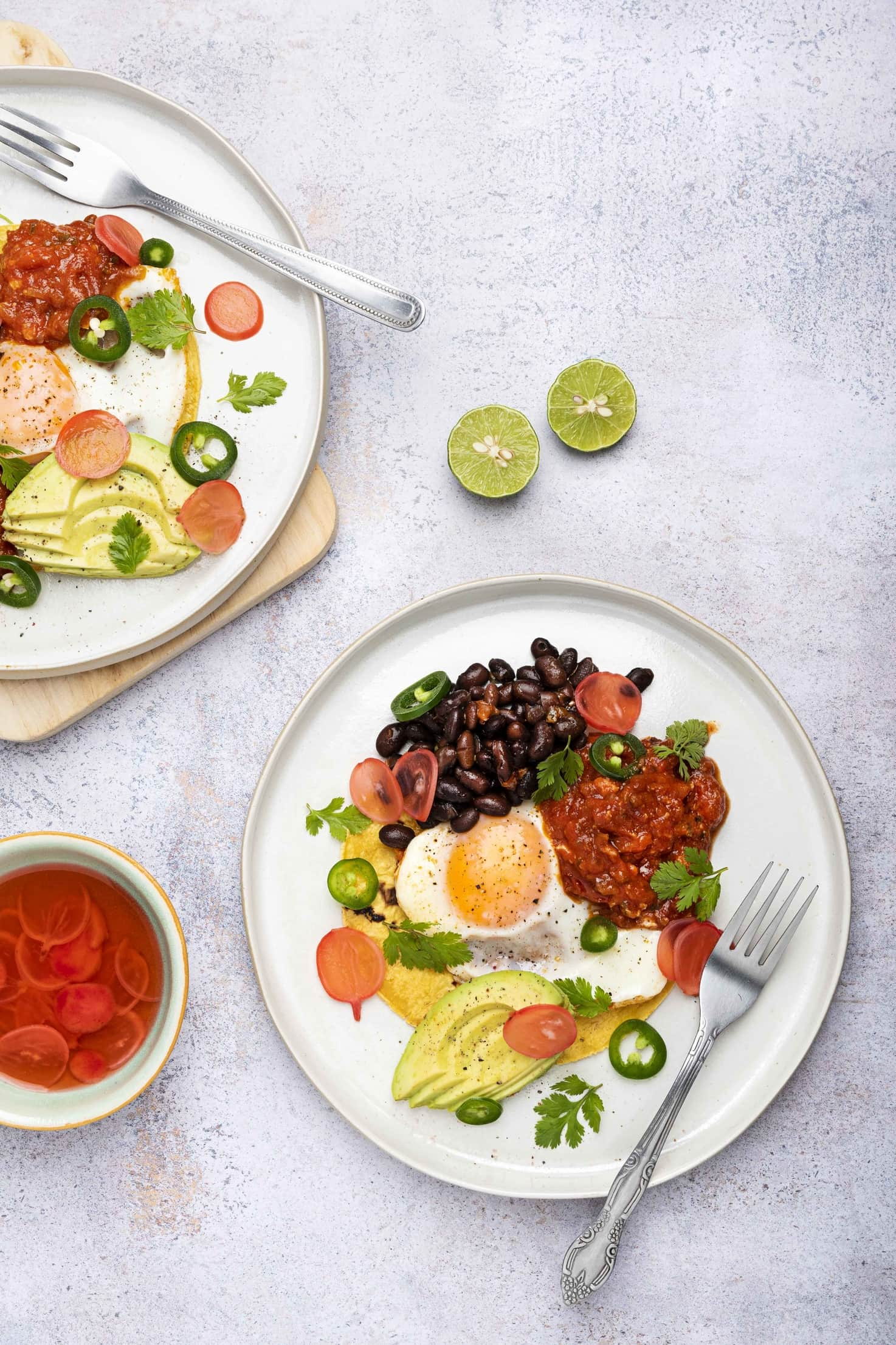 Two plates of huevos rancheros, served with radish pickle and two limes   Hurry The Food Up