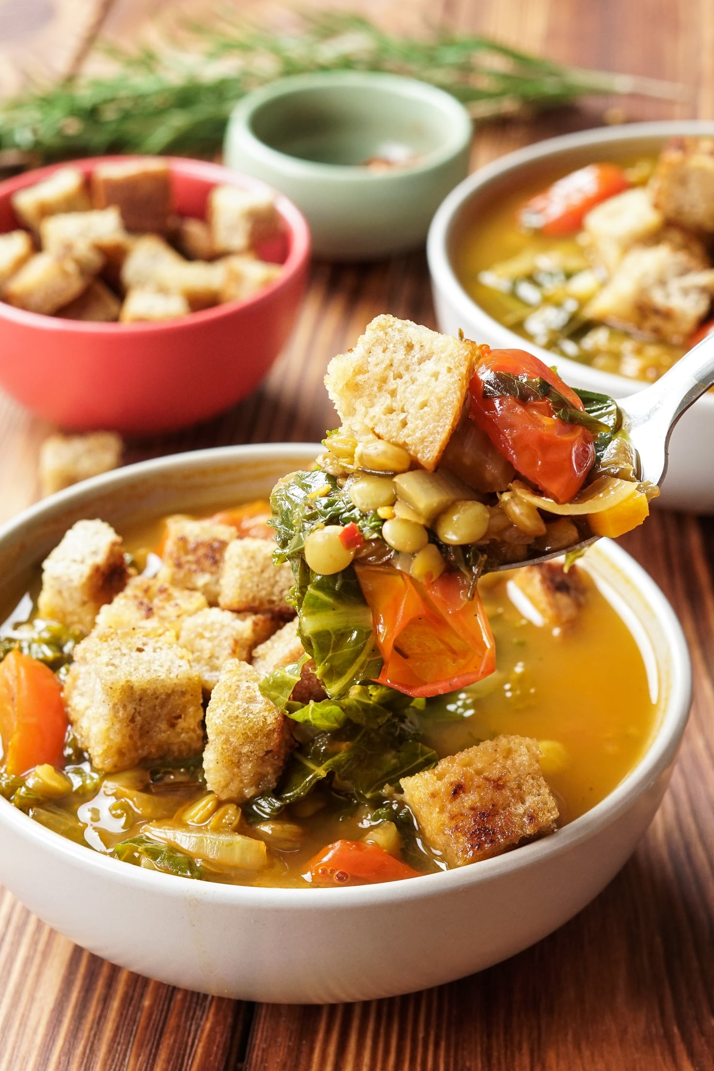 Two bowls of lentil and vegetable soup are on a wooden table. Behind them is a bowl of croutons and a smaller bowl of spices. Behind them is a sprig of rosemary. In the foreground a spoonful of lentil vegetable soup is held up   Hurry The Food Up