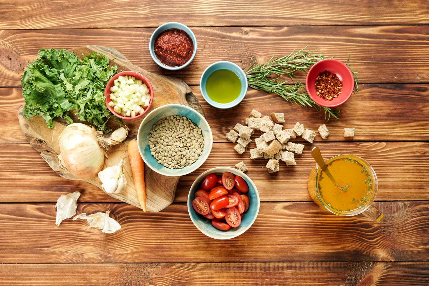 The ingredients for the lentil vegetable soup are laid out on a wooden table. These include stock, chopped bread, chilli flakes, olive oil, sprigs of rosemary, green lentils, chopped onion, tomato paste, chopped kale, a small carrot and some garlic   Hurry The Food Up