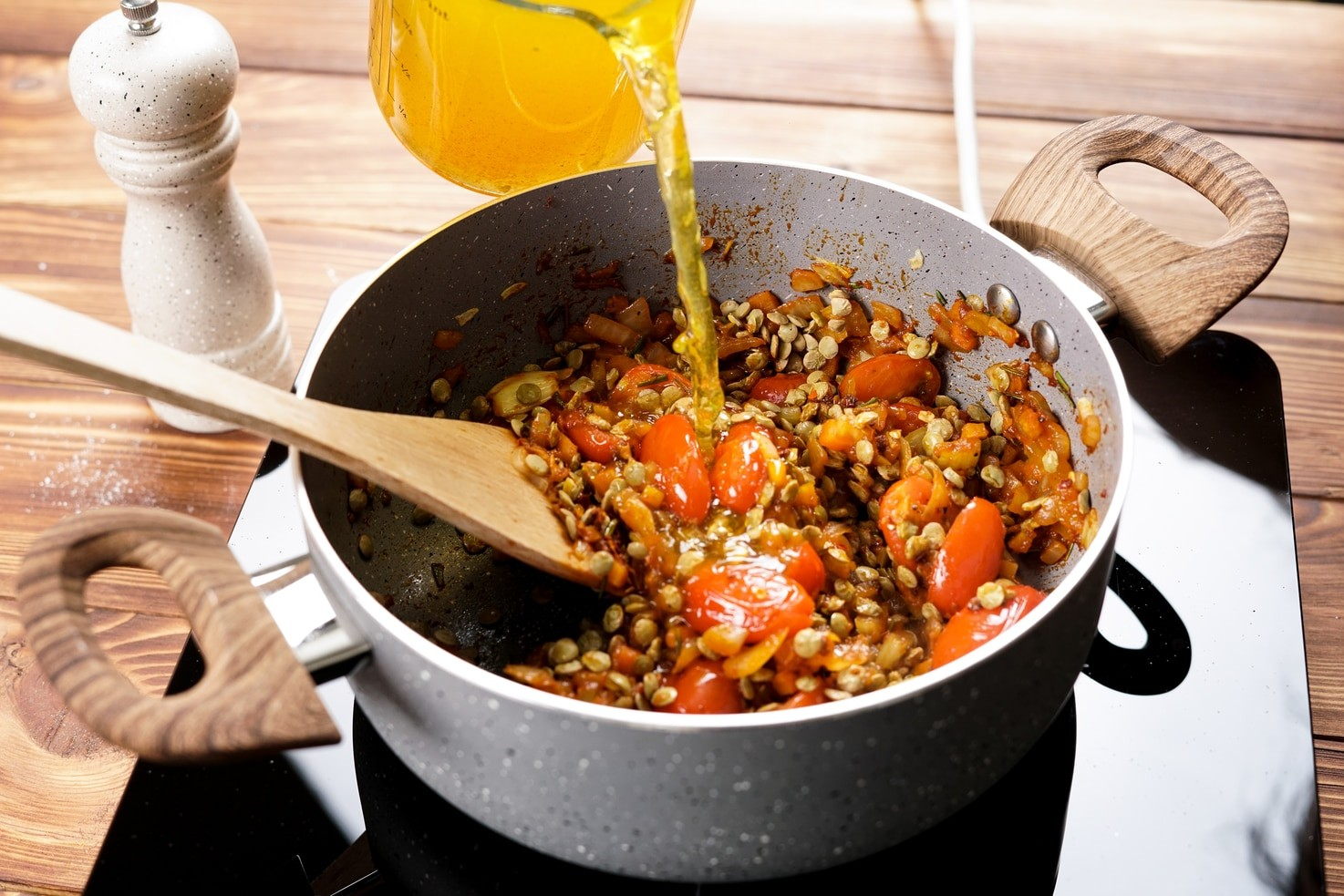 A stage in the preparation of the soup. The pan contains the lentils cherry tomatoes and onion mix, stock is being added. A wooden spoon is in the pan, ready for mixing, and there is a pepper grinder in the background.   Hurry The Food Up