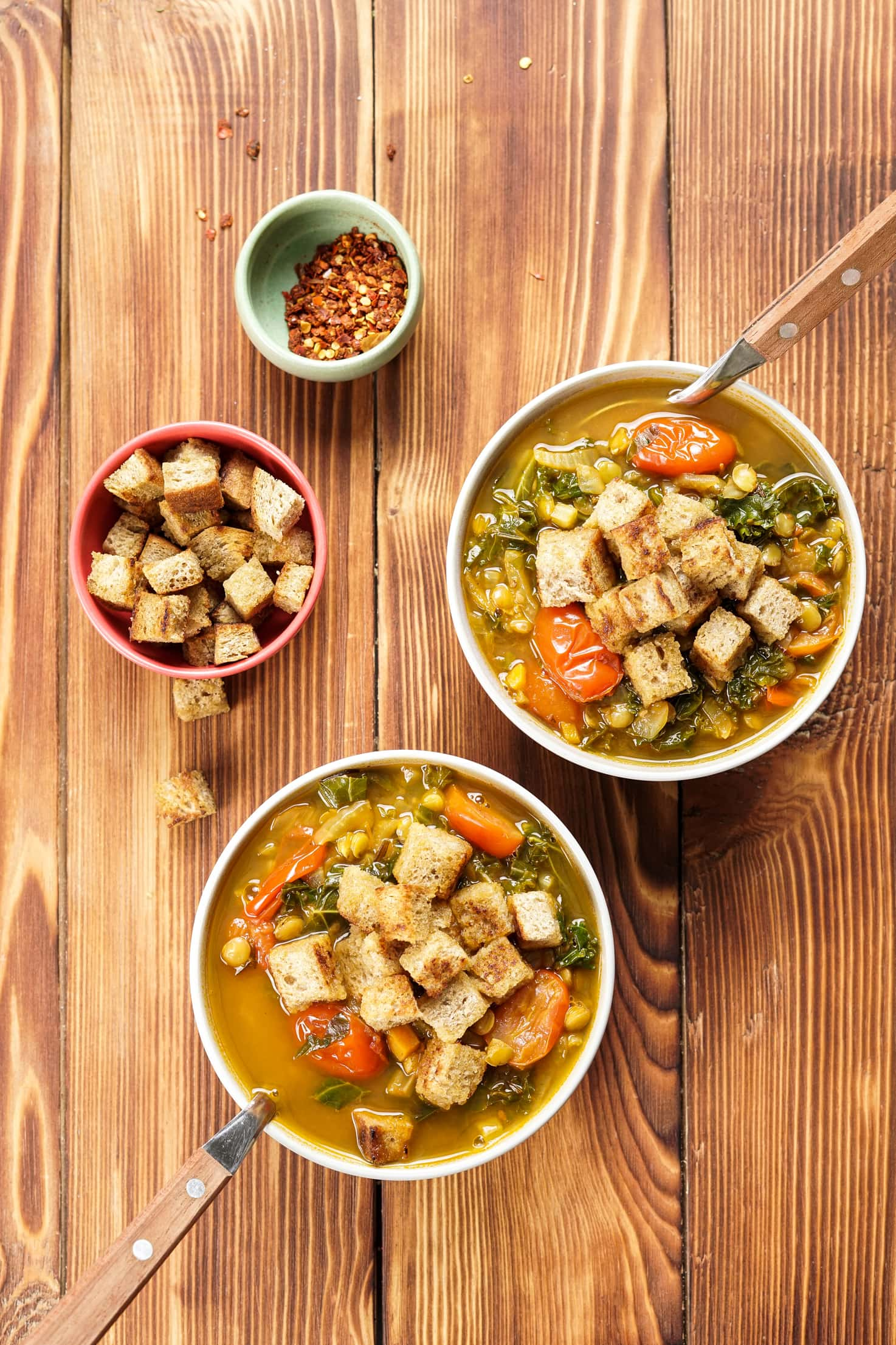 Two bowls of lentil soup on a wooden table. Next to them to the left are a bowl of croutons and a bowl of chilli flakes   Hurry The Food Up