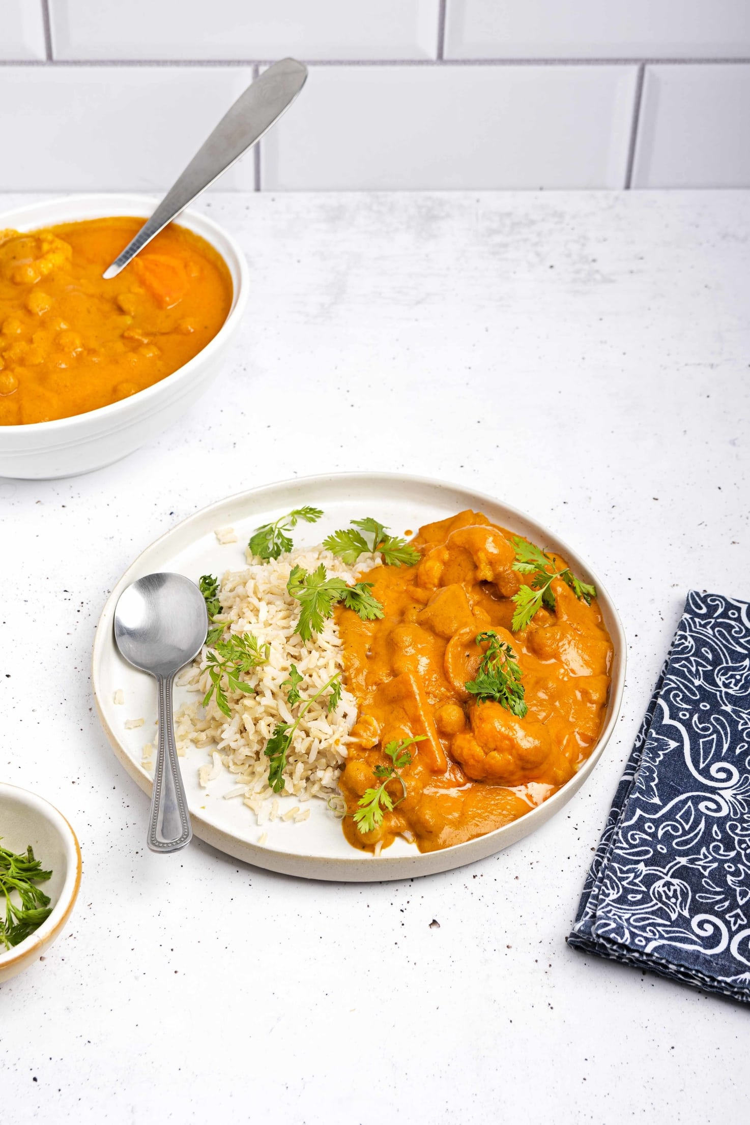 Vegan Tikka Masala served with a spoon on a plate, accompanied by brown rice and garnished with parsley. There is another bowl of tikka masala in the top left hand corner and a small bowl of chopped parsley in the bottom left hand corner   Hurry The Food Up