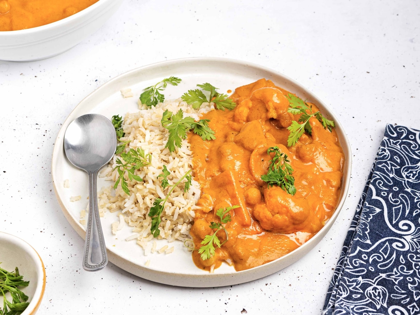 The vegan tikka masala is served on a plate with rice and garnished with parsley. The plate has a spoon on it, there is a tea towel in the right hand corner and you can see a bowl of parsley and another bowl of tikka masala in the left hand corners   Hurry The Food Up