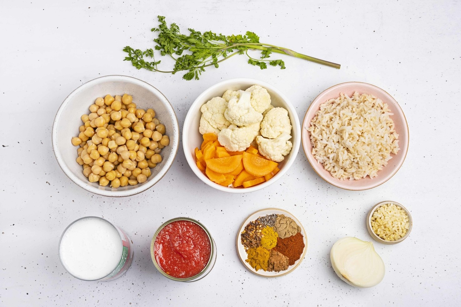 The ingredients for the vegan tikka masala are laid out in bowls, including chickpeas, cauliflower and carrots, brown rice, coconut milk, tomatoes, a selection of spices, half an onion, minced garlic and a sprig of parsley   Hurry The Food Up