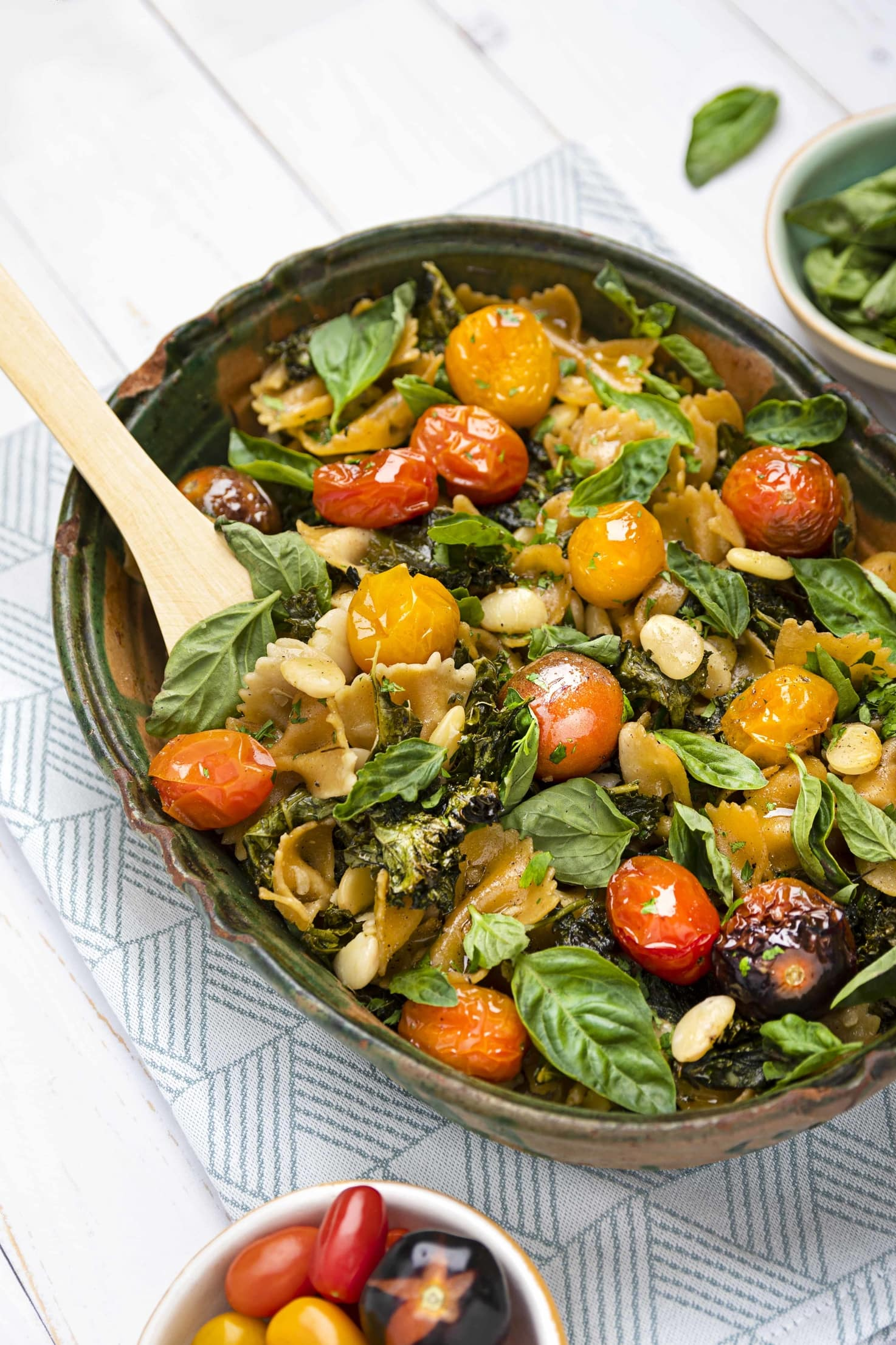 The casserole is in its dish on a table, with a wooden spoon in it lifting up some of the bean, tomato, kale and pasta mix | Hurry The Food Up