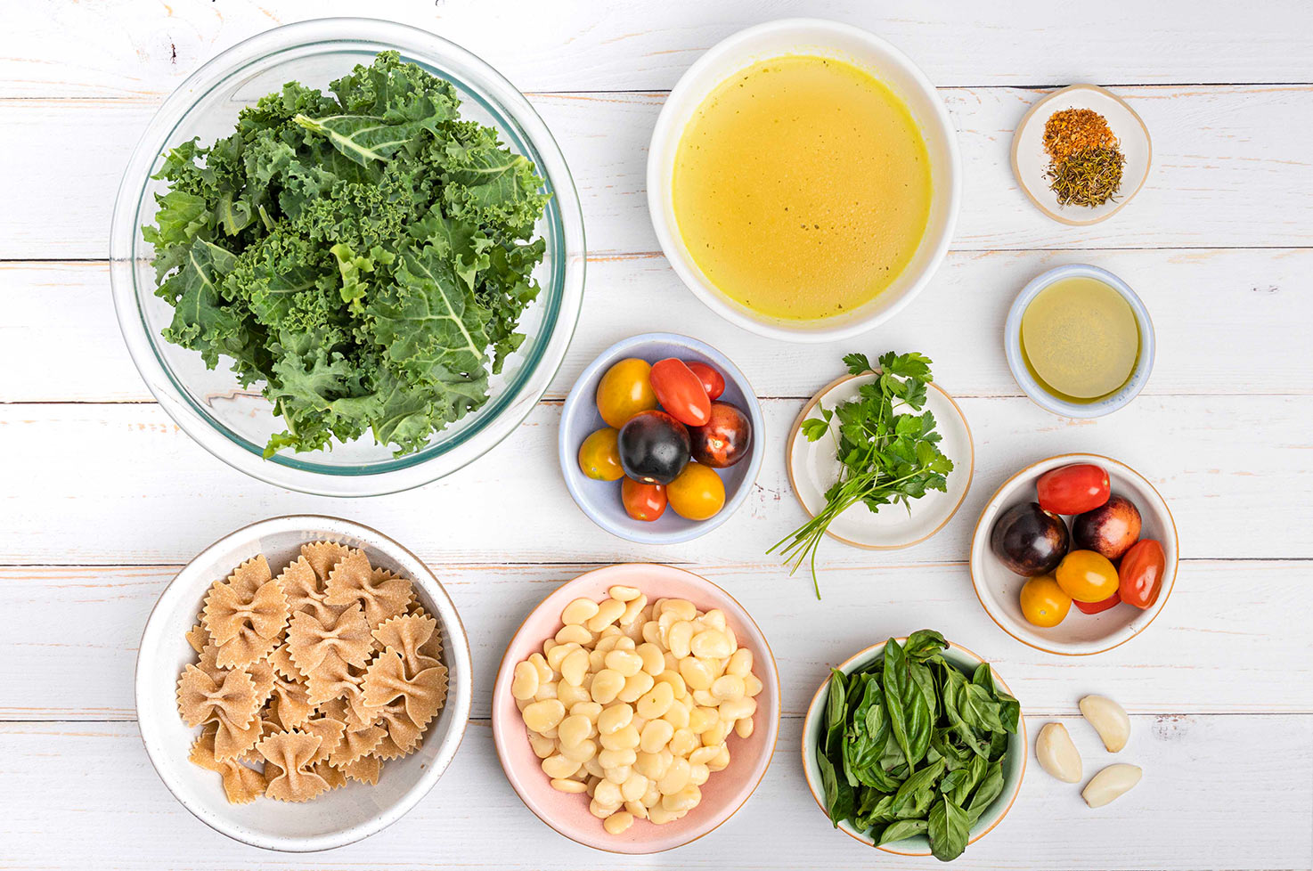 The ingredients for a casserole are laid out on a table, including chopped kale, vegetable stock, tomatoes, beans, pasta, basil, parsley, other spices garlic cloves | Hurry The Food Up