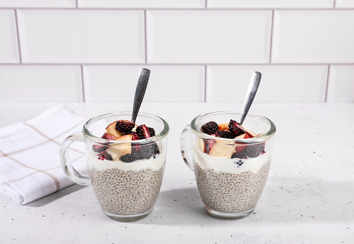 Two cups of the prepared chia pudding with toppings and teaspoons | Hurry The Food Up