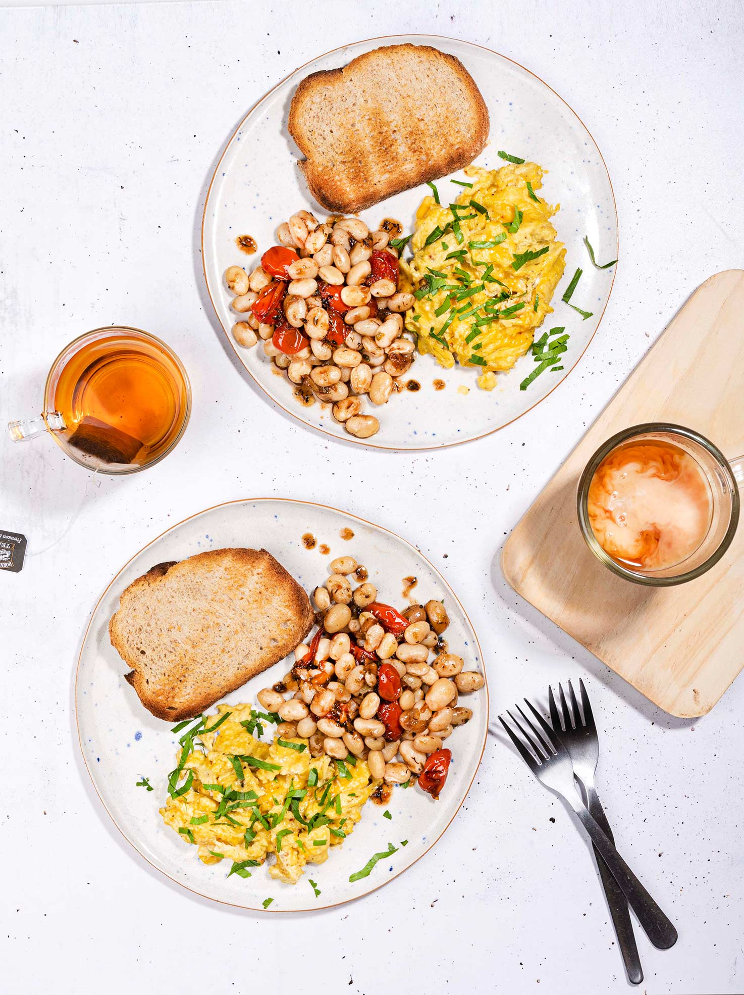 Eggs and beans breakfast is served with whole grain toasts on two plates that are on the white table with two forks and a cup of tea and coffee with milk | Hurry The Food Up